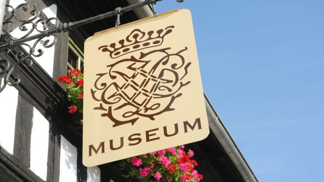 Das Eingansschild vom Bach-Stammhaus ist ein helles beige, auf dem dunkelbraun oben das Bach-Siegel zu sehen ist, unten in Großbuchstaben das Wort Museum. Im Hintergrund am Bachhaus sieht man Geranien, darüber blauen Himmel. Das Wappen ist zwei mal die Bu