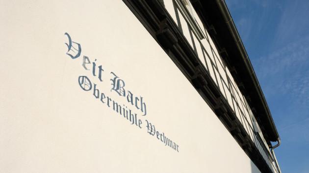 """Man schaut auf den aufgemalten Schriftzug auf der Veit-Bach-Mühle im Bachort Wechmar. Dort steht: """"Veit Bach"""", darunter etwas kleiner Obermühle Wechmar. Oben sieht man Fachwerk, darüber blauer Himmel."""