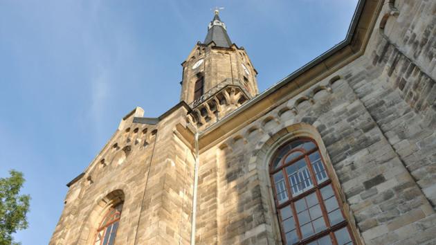 Man schaut  hinauf Richtung Kirchturmspitze. Es ist die Sankt Viti Kirche, unten kann man ein Teil des Kirchengebäudes sehen, mit einem Fenster. Ganz oben ist die Spitze. Es ist blauer Himmel ohne Wolken und die Kirche liegt in der Sonne.