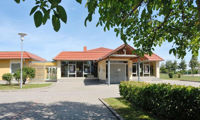 Im Foto zum Bachort Wechmar ist in der Mitte ein einstöckiges Gebäude mit roten Ziegeln. Davor ist ist ein Pakrplatz, rechts eine Hecke, oben noch Blätter vom Baum: es ist die Verwaltung von Wechmar.