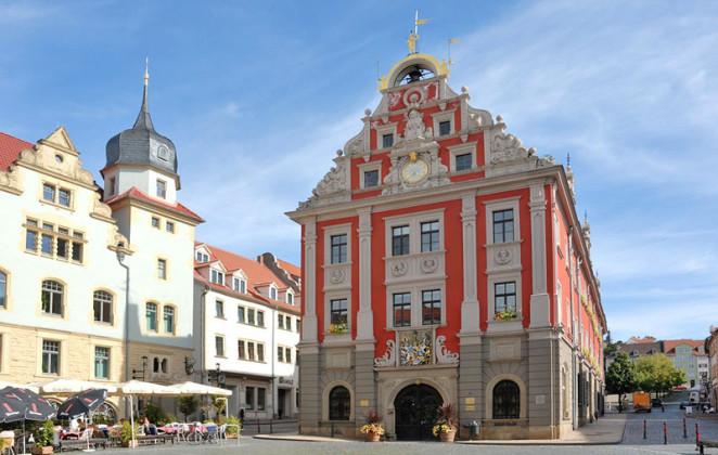 Man sieht das Rathaus der Bachstadt Gotha im Bild. Es ist ein historischer Bau, steht frei und das Wetter ist perfekt. Daneben ist ein Gebäude mit Rastaurant und Schirmen. Alles ist im Barockstil.