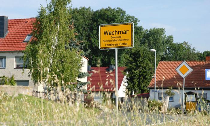 Man sieht über ein Getreidefeld auf den Ortsrand vom Bachort Wechmar. In der Bildmitte ist das gelbe Ortseingansgsschild. Dahinter sieht man Wohnhäuser, der Himmel ist wolkenlos.