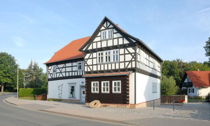 In der Bildmitte des Fotos ist die Veit-Bach-Mühle im Bachort Wechmar. Es ist ein Fachwerkbau mit roten Ziegeln. Eine Straße führt um die Veit-Bach-Mühle herum. Dahinter mittel entfernt ist ein Wohnhaus zu sehen.