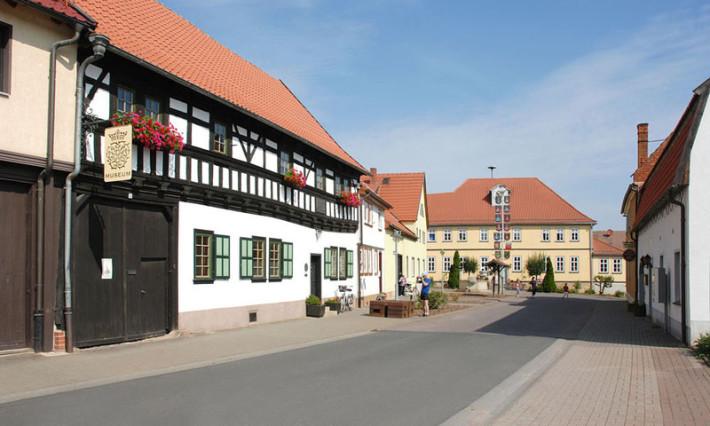 Im Foto zum Bachort Wechmar sieht man links das Bach-Stammhaus. In der Mitte verläuft eine Straße nach hinten, rechts der Gehweg. Im Hintergund ist ein gelber Bau zu sehen: das Gasthaus Goldener Löwe.