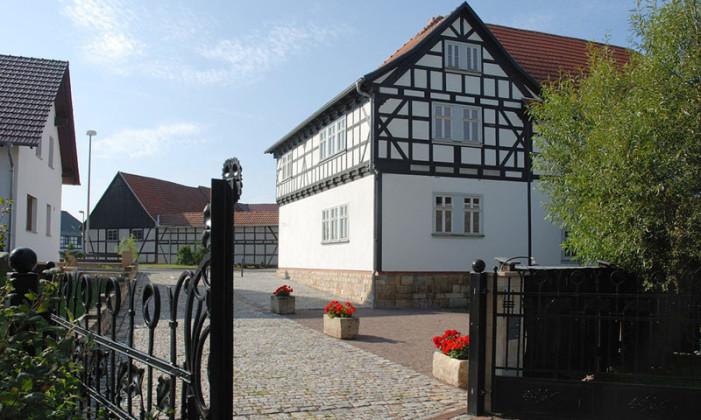 Im Bachort Wechmar sieht man die Veit-Bach-Mühle von der Rückseite. Im Vordergrund: ein schmiedeeisernes Tor, rechts ein Baum, links ein Wohnhaus und über der Straße ist eine Scheune zu sehen.