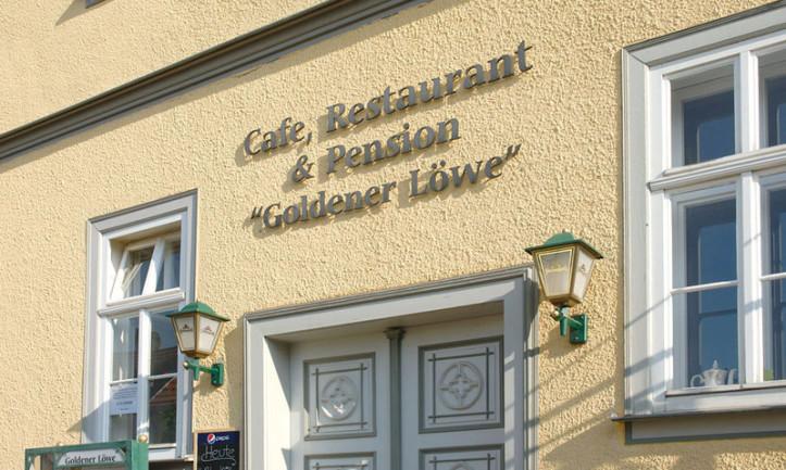 Im Foto sieht man eine Nahaufnahme der Schrift des Gasthauses Goldener Löwe auf dem gelben Gebäude. Cafe, Restaurant und Pension sind im Bachort Wechmar. Rechts und links sind Sprossenfenster.
