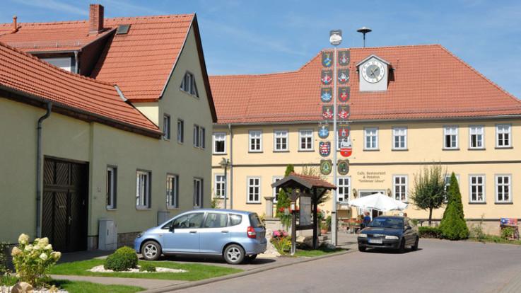 Ein Blick auf die Pension, das Restaurant und den Gasthof Goldener Löwe, davor ist ein Wappen-Baum. Im Bild sieht man auch zwei parkende Autos. Die Sonne scheint, der Himmel ist blau. Vor dem gelben Gebäude ist ein Schirm.