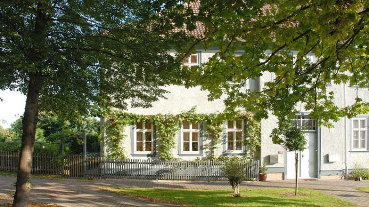 Durch leichtes hellgrünes Baumlaum blickt man auf ein restaurierte Gebäude mit einm Zierzaun davor: Es ist das ehemalige Schulhaus in Wechmar, wo auch Bachs unterrichteten. Im Vordergrund ist Gras und Gehweg.